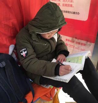 山东大哥拍心酸照片,孩子电动车上写作业