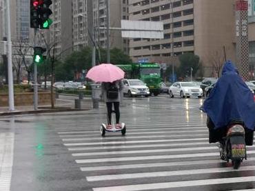 """大妹纸,你也太肆意了!雨天打粉伞,踩个""""风火轮""""。"""