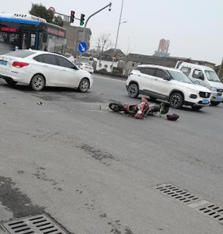 电瓶车闯红灯被小车撞倒,幸好他伤得不重